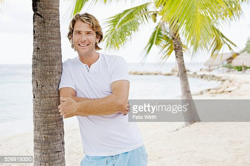 Portrait of man leaning against palm tree : Foto stock