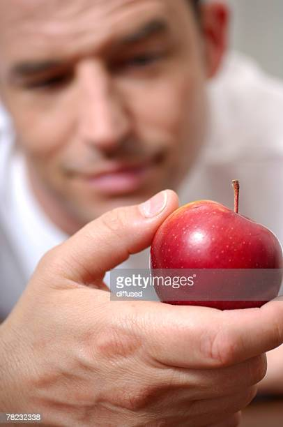 portrait of man looking at red apple