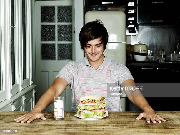 Portrait of man looking at sandwich