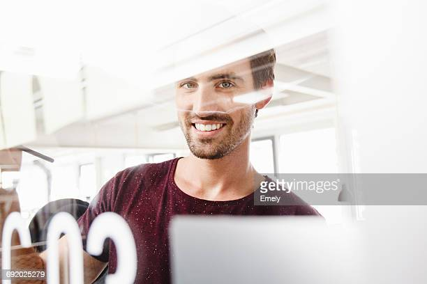 Portrait of man looking through glass at camera, smiling