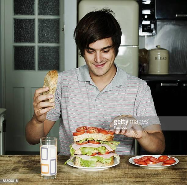 Portrait of man making a sandwich