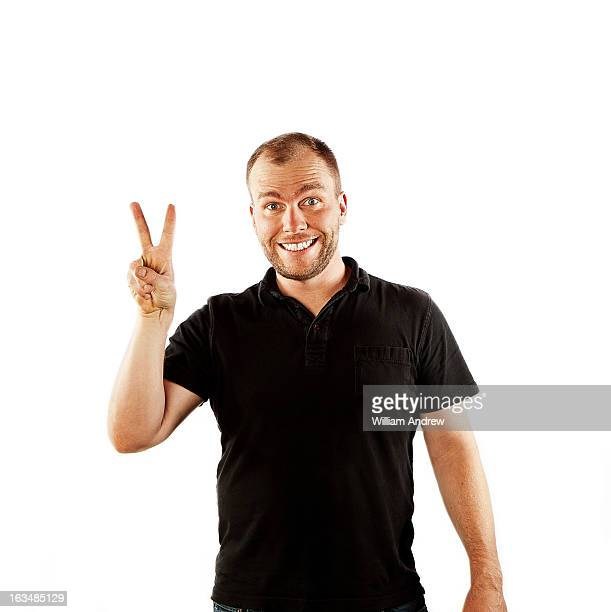 Portrait of man making peace sign