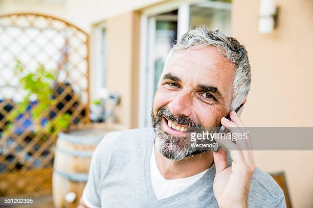 Portrait of man on his balcony telephoning with smartphone