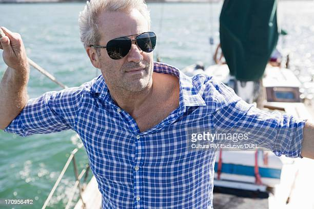 Portrait of man on yacht wearing checked shirt and sunglasses