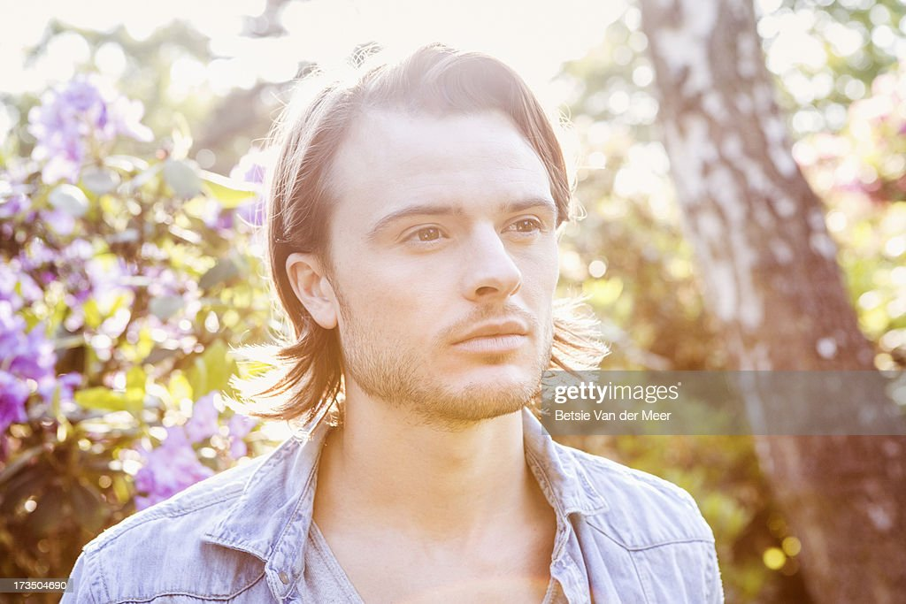 Portrait of man outdoors, bathed in sunlight. : Stock Photo
