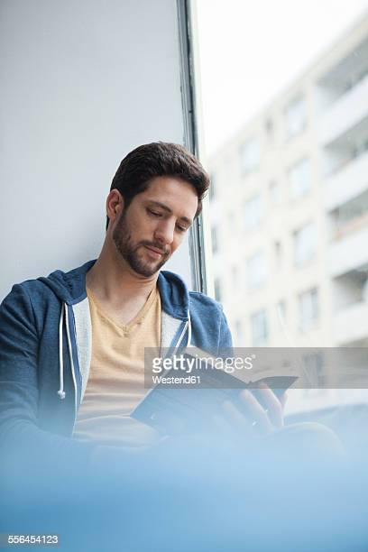 Portrait of man reading a book at the window