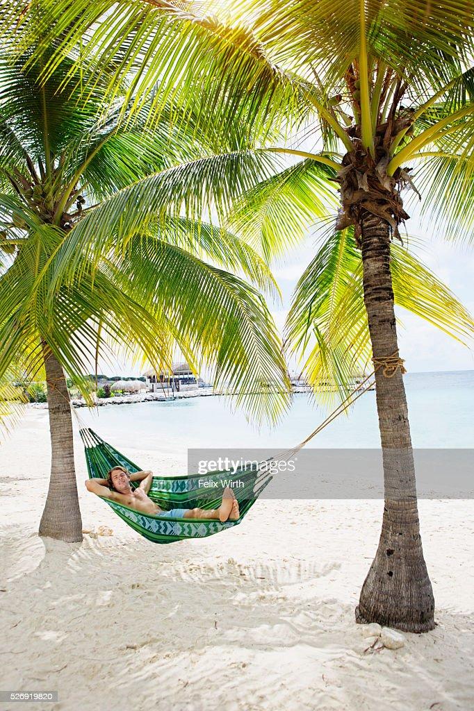 Portrait of man relaxing in hammock on beach : Foto de stock