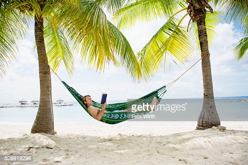 Portrait of man relaxing in hammock on beach reading book : ストックフォト