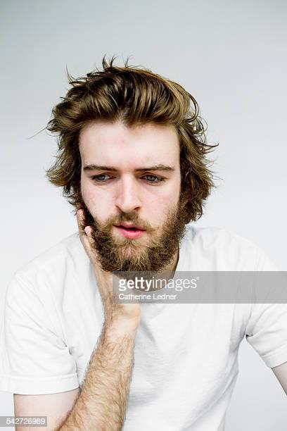 Portrait of man rubbing beard