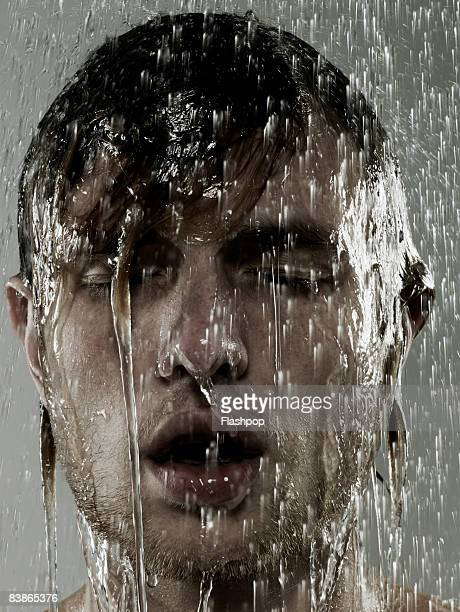Portrait of man showered with water