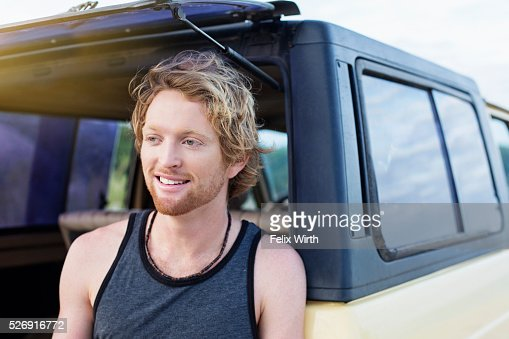 Portrait of man sitting at back of truck : Stockfoto