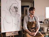 Portrait of man sitting by sketch in art class