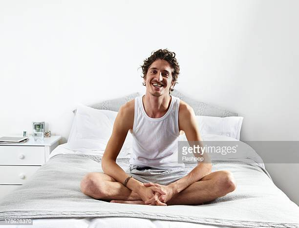 Portrait of man sitting on bed