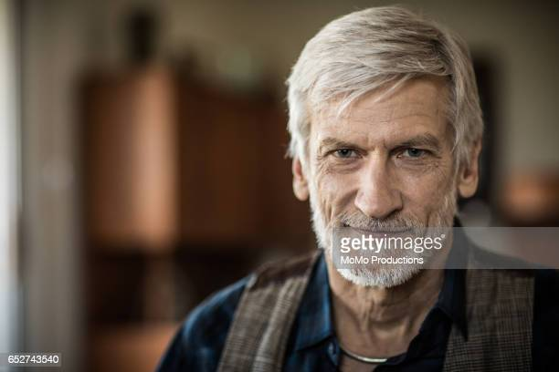 Portrait of man (60yrs) sitting on couch at home