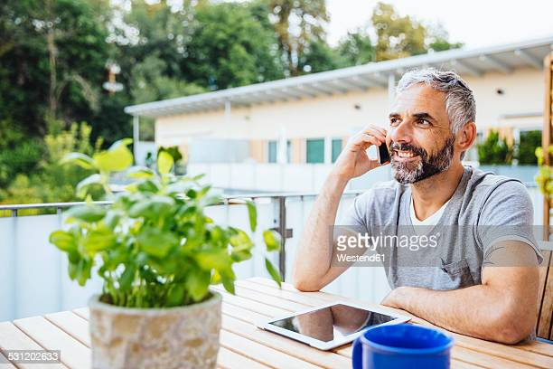 Portrait of man sitting on his balcony telephoning with smartphone