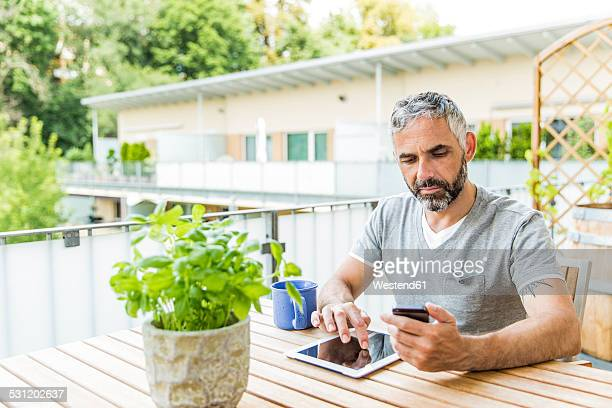 Portrait of man sitting on his balcony using smartphone and digital tablet