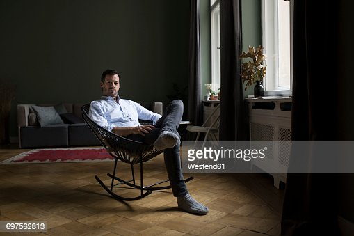 Portrait of man sitting on rocking chair in his living room
