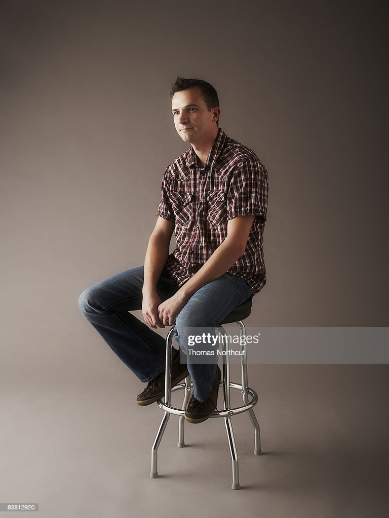 Portrait of man sitting on stool