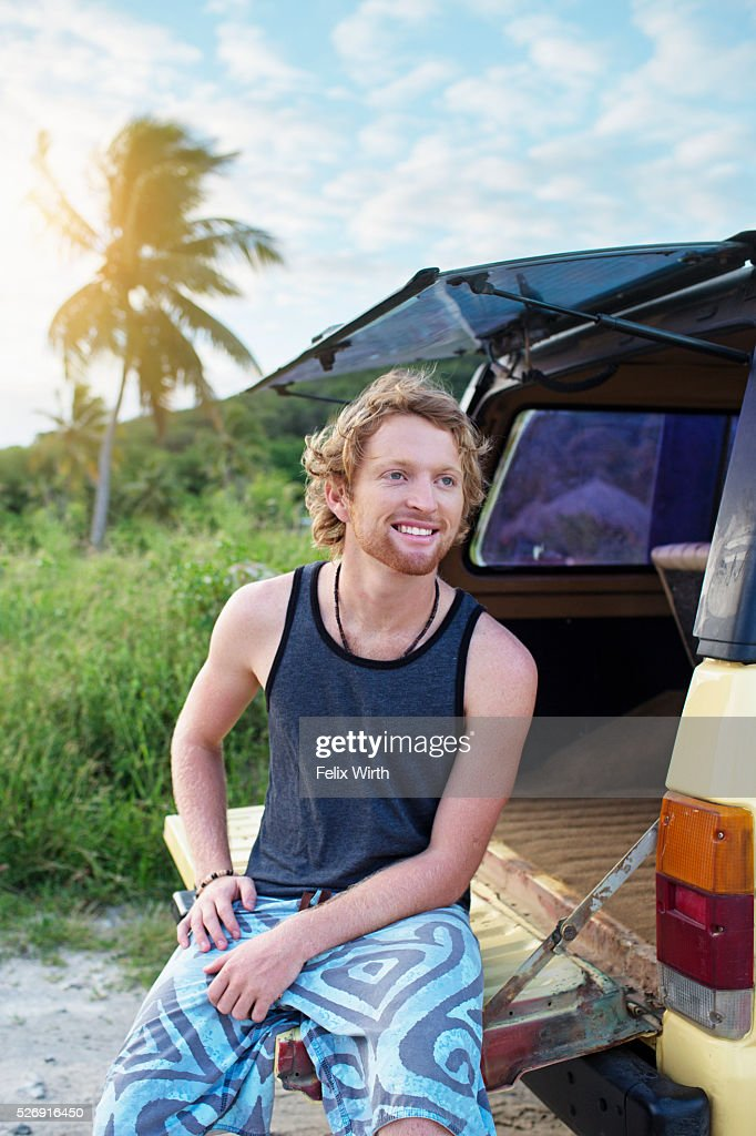 Portrait of man sitting on tailgate of truck : Stock-Foto