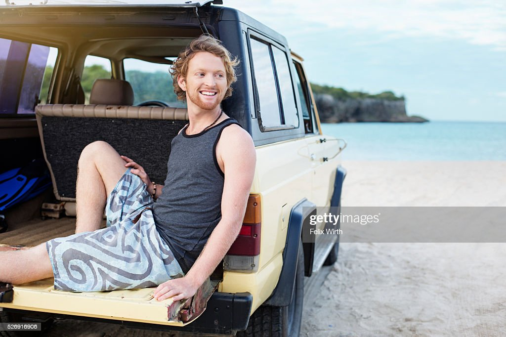 Portrait of man sitting on tailgate of truck : Foto de stock