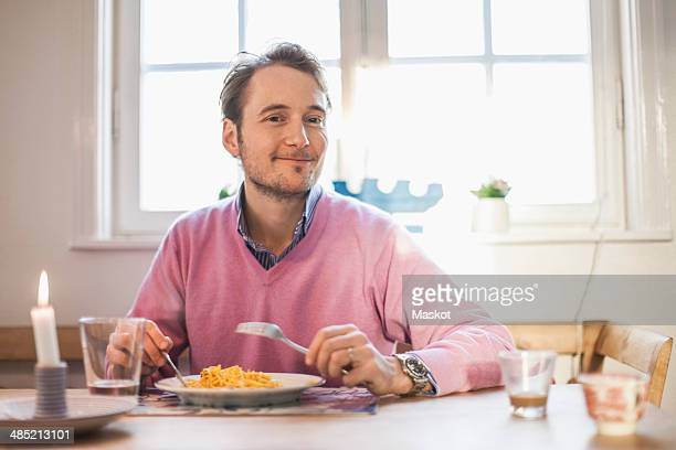 Portrait of man smiling while eating pasta