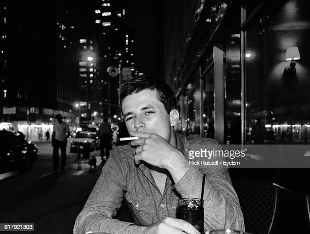 Portrait Of Man Smoking At Sidewalk Cafe In City During Night