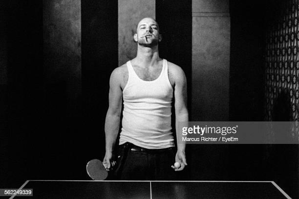 Portrait Of Man Smoking Cigarette While Playing Table Tennis