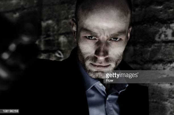 Portrait d'un homme debout à côté de mur de briques