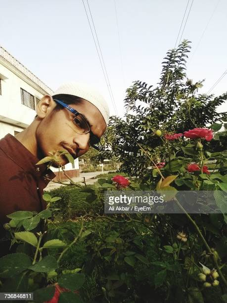 Portrait Of Man Standing By Flowers And Plants