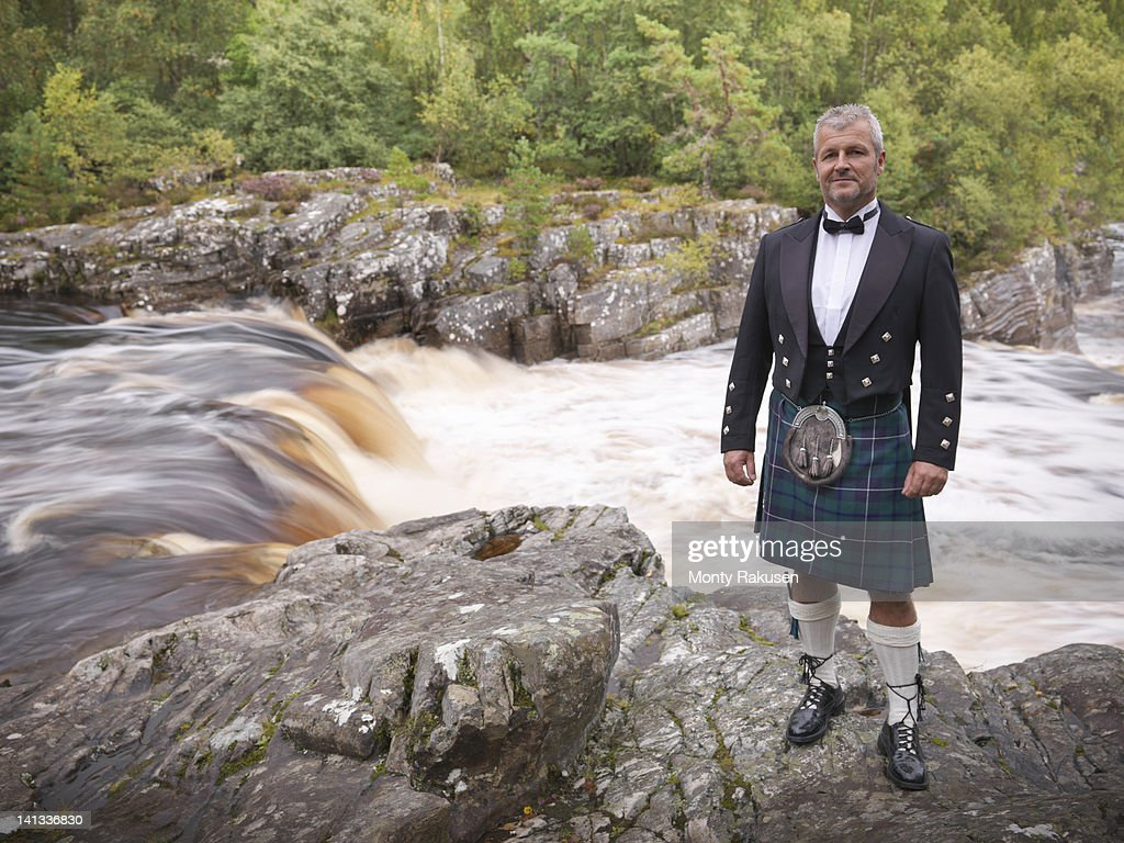 Portrait of man standing by flowing river in traditional Scottish Prince Charlie outfit with Douglas Modern Tartan