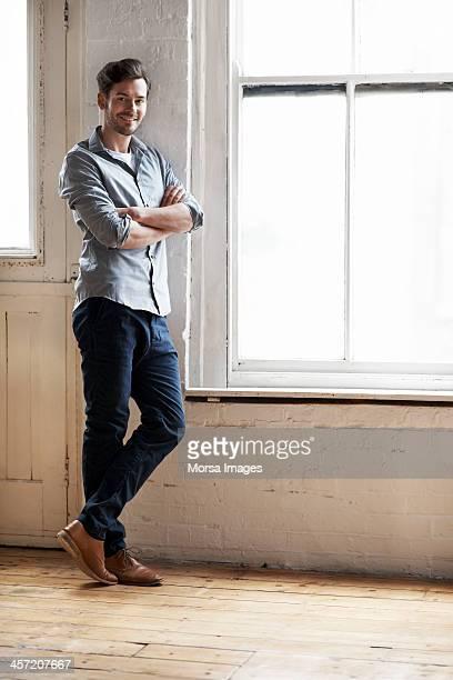 Portrait of man standing by window