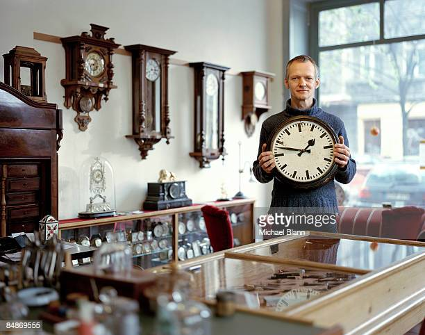 portrait of man standing holding clock in shop