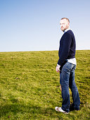 Portrait Of Man Standing In Field, Looking Back