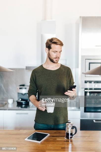 Portrait of man standing in kitchen looking at cell phone