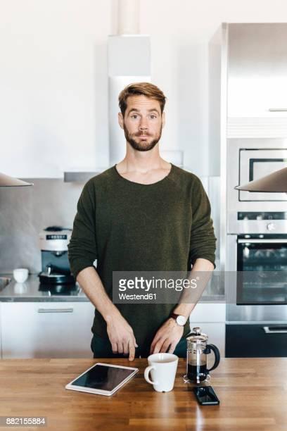 Portrait of man standing in kitchen raising his eyebrows