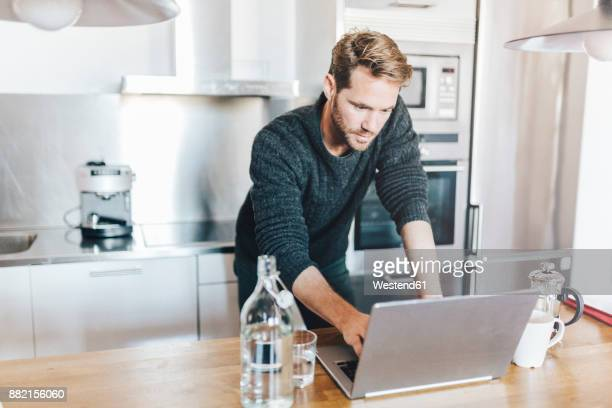 Portrait of man standing in kitchen using laptop