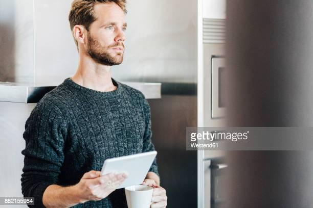 Portrait of man standing in kitchen with tablet and coffee mug