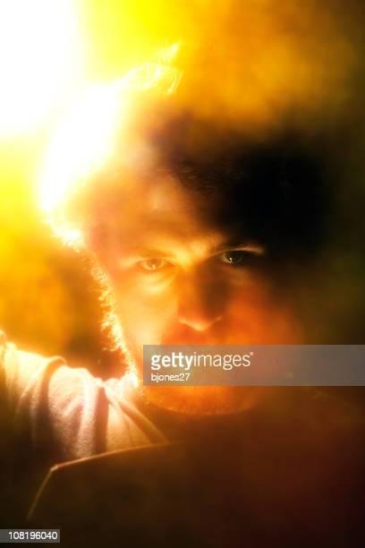 Portrait d'un homme entouré de lumière jaunes et Orange