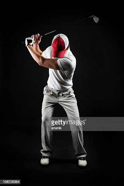 Portrait of Man Swinging Golf Club, Isolated on Black