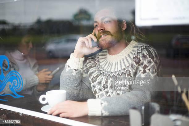 ポートレートを使用し、電話で話している男性のカフェ
