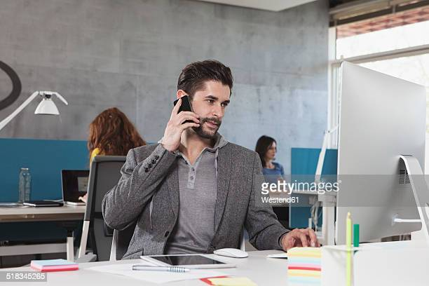 Portrait of man telephoning with his smartphone at his workplace in the office