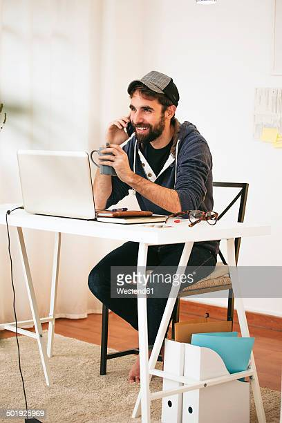 Portrait of man telephoning with smartphone at modern home office