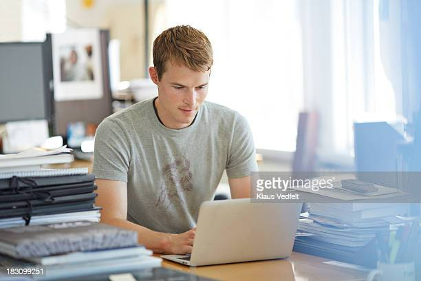 Portrait of man typing on laptop at his desk