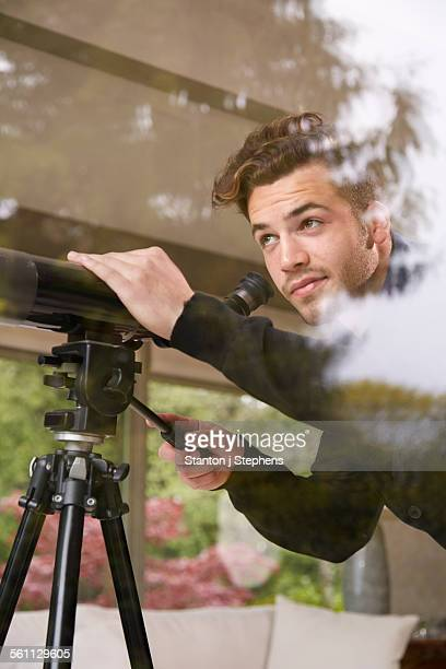 Portrait of man using telescope looking out of window