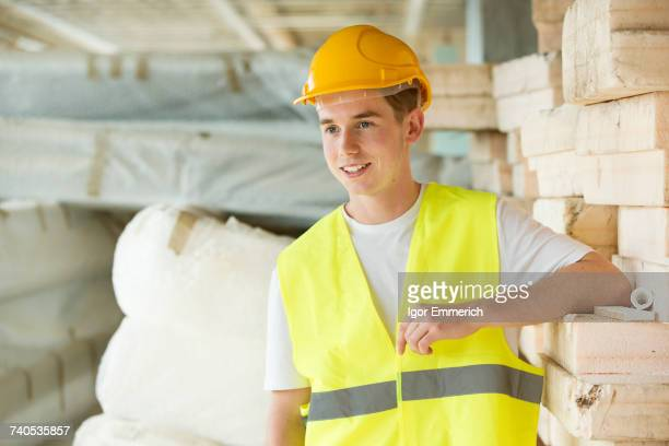 Portrait of man wearing hard hat and hi vis vest, standing beside building materials
