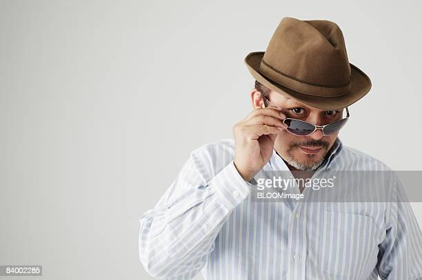 Portrait of man wearing hat and sunglasses, close-up, studio shot
