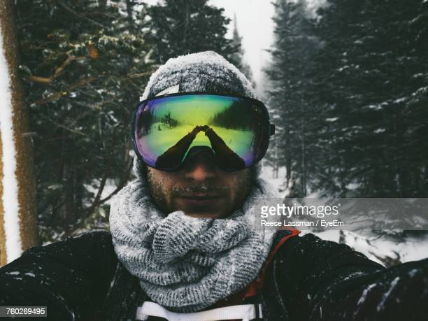 Portrait Of Man Wearing Ski Goggles With Reflection While Standing Against Trees During Winter
