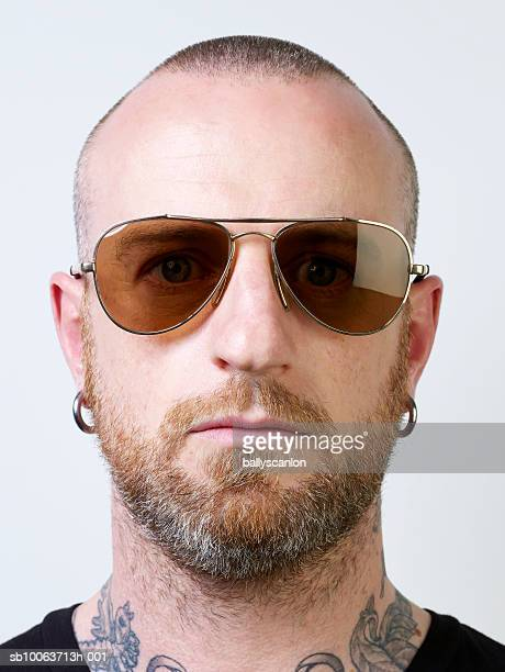Portrait of man wearing sunglasses, white background