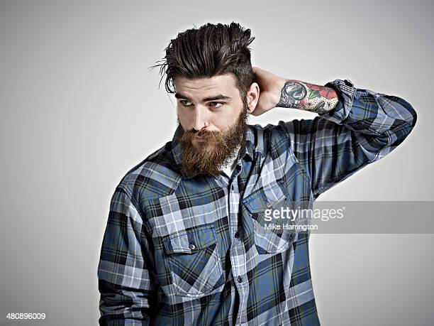 Portrait of man with beard, tattoos & check shirt.