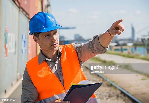 Portrait of man with blue safety helmet checking cargo containers